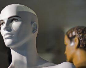 Bald white mannequin in a storefront window by night. It has a clear, male model like facial structure emphasized by the bright spot light coming from its right side. In the back there's another blurred brown figure with curly hair.