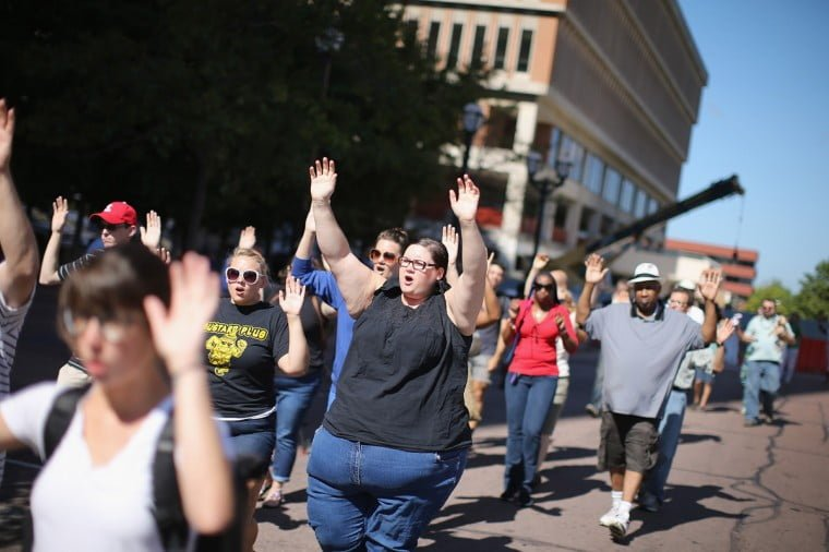 Protesters all over Ferguson approach police with hands up to show no weapons are concealed.