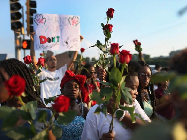 Protesters all over Ferguson give out roses as a sign of morning