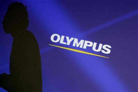 Staff member is silhouetted on a projector screen displaying a logo of Olympus Corp before a news conference in Tokyo
